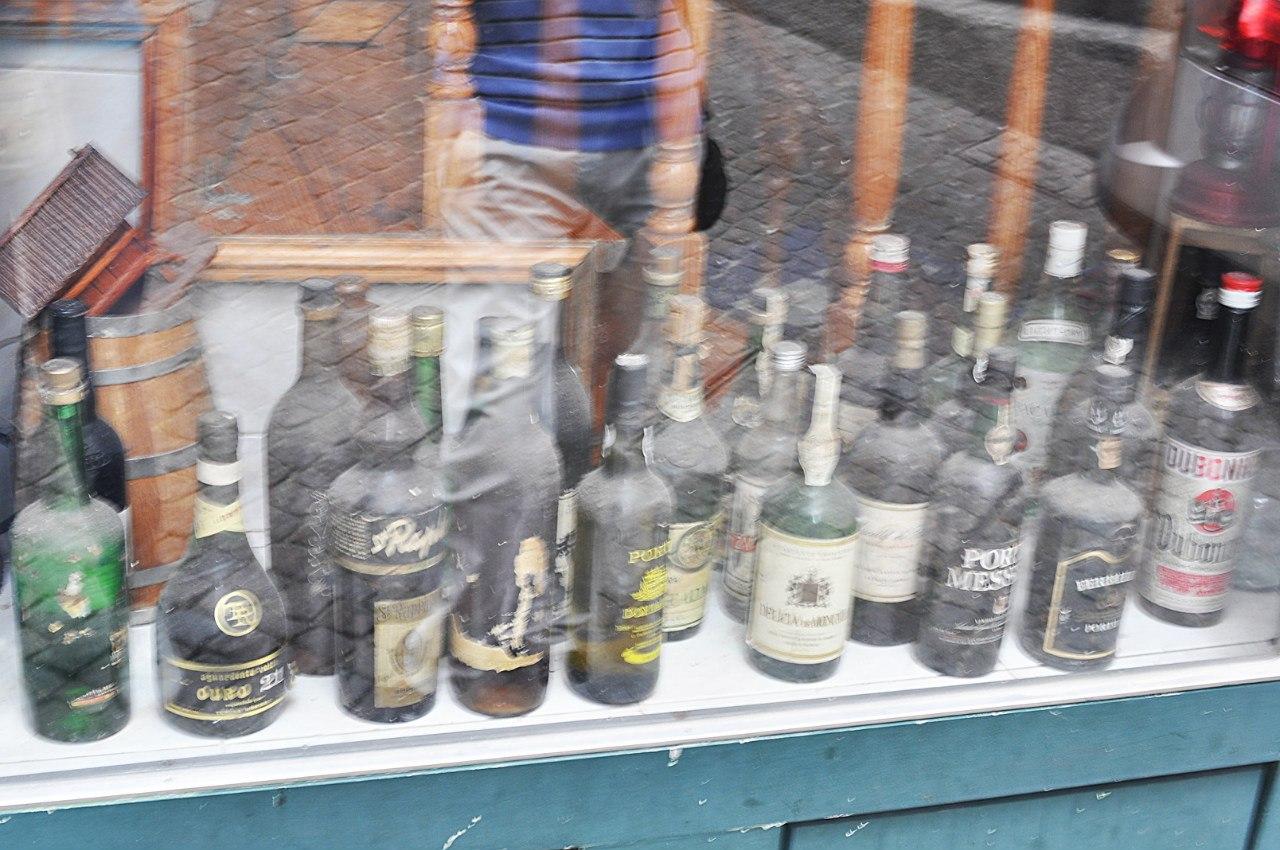 запыленные бутылки портвейна в магазине